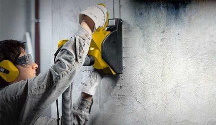 Un travailleur frappe des stroboscopes dans le mur