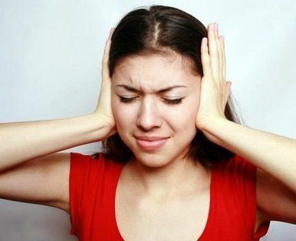 Meitene aizsedza ausis ar rokām