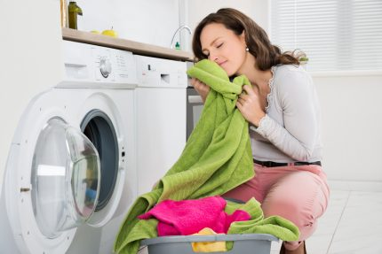 Woman takes laundry out of the washer