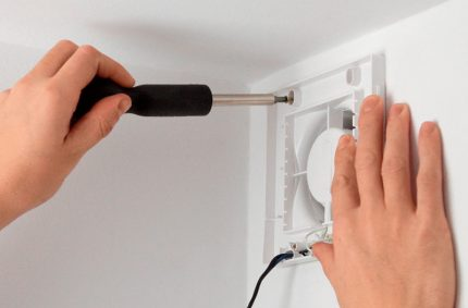The master screws the exhaust fan with a screwdriver