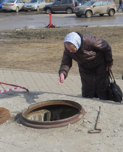 Elderly woman looks in the sewer