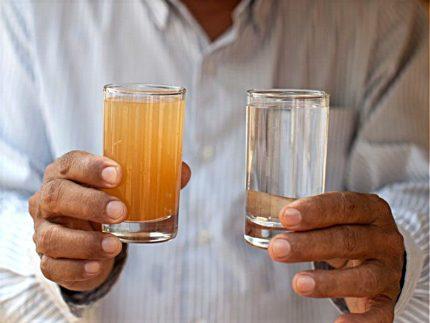 L'homme tient des verres avec de l'eau sale et propre.