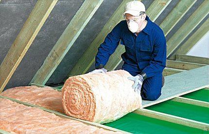 Le maître met l'isolant en laine de verre