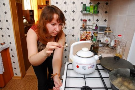 Woman lights a burner with a match