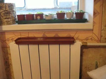 Ūdens panna uzstādīta uz radiatora
